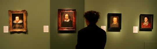 "A woman looks at  portraits of William Shakespeare on display at the National Portrait Gallery in London as part of an exhibition, ""Searching for Shakespeare,"" of portraits and manuscripts from Shakespeare's lifetime, in 2006.  From left: the portrait  known as the Janssen portrait dated 1610. Second from the left, a painting attributed to a little-known artist named John Taylor, dated by experts to between 1600 and 1610, is the so-called Chandos portrait. The painting second from right is known as the Sanders portrait, dated 1603,  and the artwork, right, is known as Grafton portrait dated 1588. The Grafton is believed to not show the real Shakespeare."