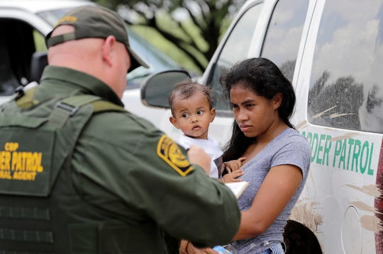 A mother migrating from Honduras holds her 1-year-old child while surrendering to U.S. Border Patrol agents after illegally crossing the border near McAllen, Texas, on June 25, 2018.