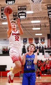 Kimberly's Levi Nienhaus-Borchert gets a layup past Oshkosh West's Caleb Fuller during a game this season.