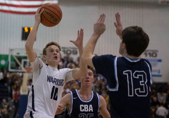 Manasquan's Benjamin Roy drives to the basket as CBA's Stephen Braunstein. Manasquan Boys Basketball vs Christian Brothers Academy  in Shore Conference Semifinal game in Toms River,  NJ. on February 21, 2019.