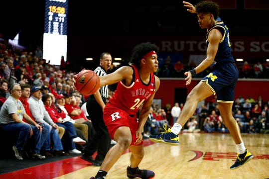 Rutgers Scarlet Knights forward Ron Harper Jr. (24) dribbles the ball against Michigan Wolverines earlier this month. Harper Jr. is wearing Rutgers' Celebrating Black Culture uniform and sneakers.