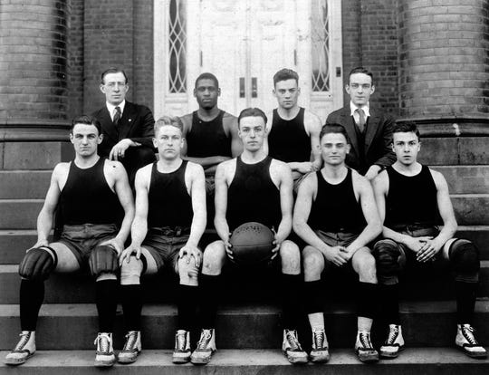 A photo of the 1916-17 Rutgers basketball team with Paul Robeson (back row, left), then a sophomore, seated next to longtime coach Frank Hill.