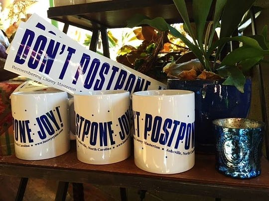 """Don't Postpone Joy"" bumper stickers and mugs are still available at Thyme in the Garden store in Asheville."