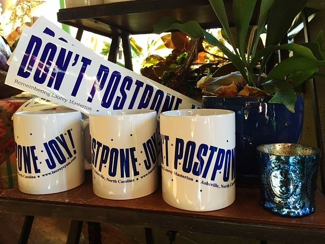 """""""Don't Postpone Joy"""" bumper stickers and mugs are still available at Thyme in the Garden store in Asheville."""