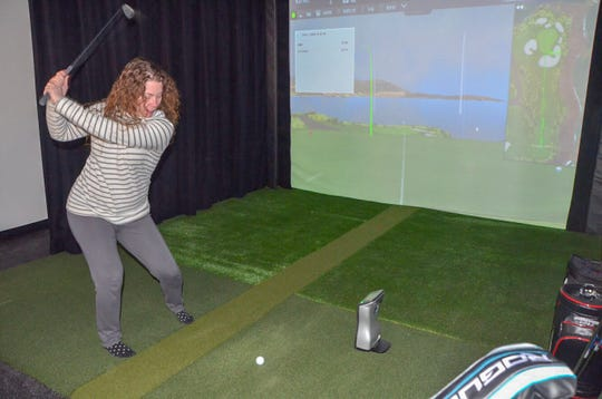 Albion resident Kelly Rice tries out the golf simulator at the new Mitchell Golf Performance Studio in downtown Albion, at 304 South Superior St., during its grand opening on Thursday, Feb. 21, 2019.