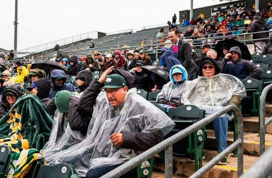 Fans at Hohokam Stadium try to cover up as rain settles in and ends up canceling a spring training baseball game between The Seattle Mariners and the Oakland Athletics after 1-1/2 innings Thursday, Feb. 21, 2019, in Mesa, Ariz.