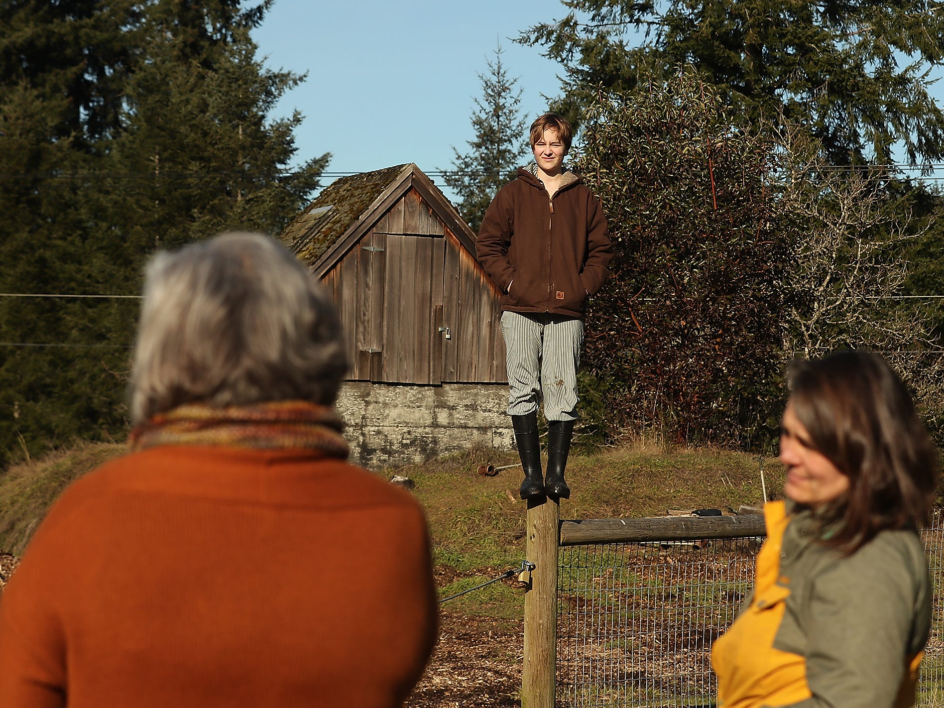 Quinn Taylor, 13, stands atop a fence post as her mother Tracy Lang (right) and Heather Burger, with Friends of the Farms, (left) chat about the plans for the Taylor family to open a hydroponic farm on Bainbridge Island's publicly-owned Johnson Farm property on Thursday, February 21, 2019.