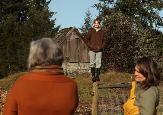 Quinn Taylor, 13, stands atop a fence post as her mother Tracy Lang, right, and Heather Burger, with Friends of the Farms, left, chat about the plans for the Taylor family to open a hydroponic farm on Bainbridge Island's publicly-owned Johnson Farm property.
