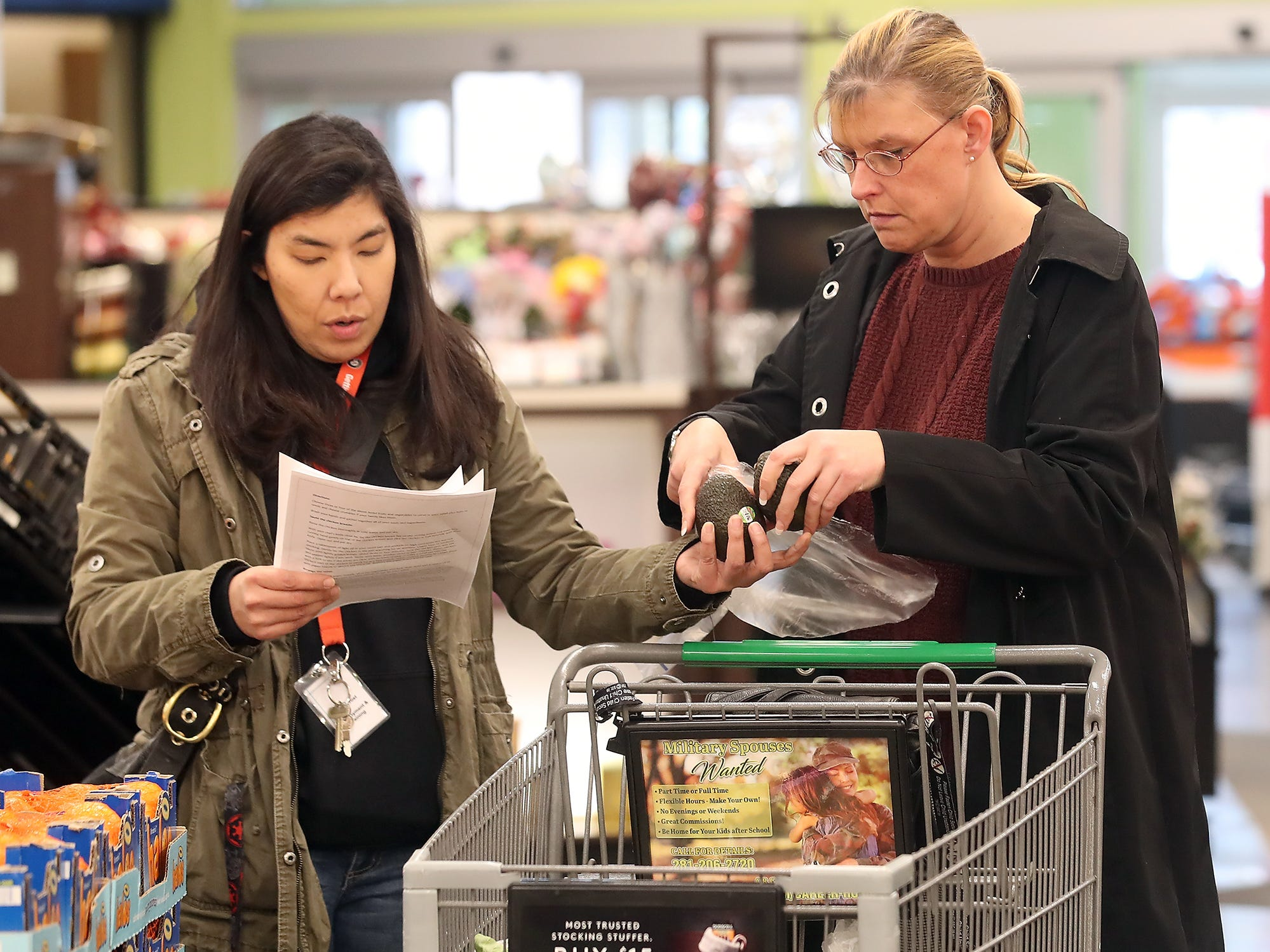 AmeriCorps Life Skills Facilitator Shin Frost (left) hands Brandy Mathews two avocados as they check off the items for salad and homemade chicken noodle soup at Fred Meyer in Bremerton on Wednesday, February 20, 2019.