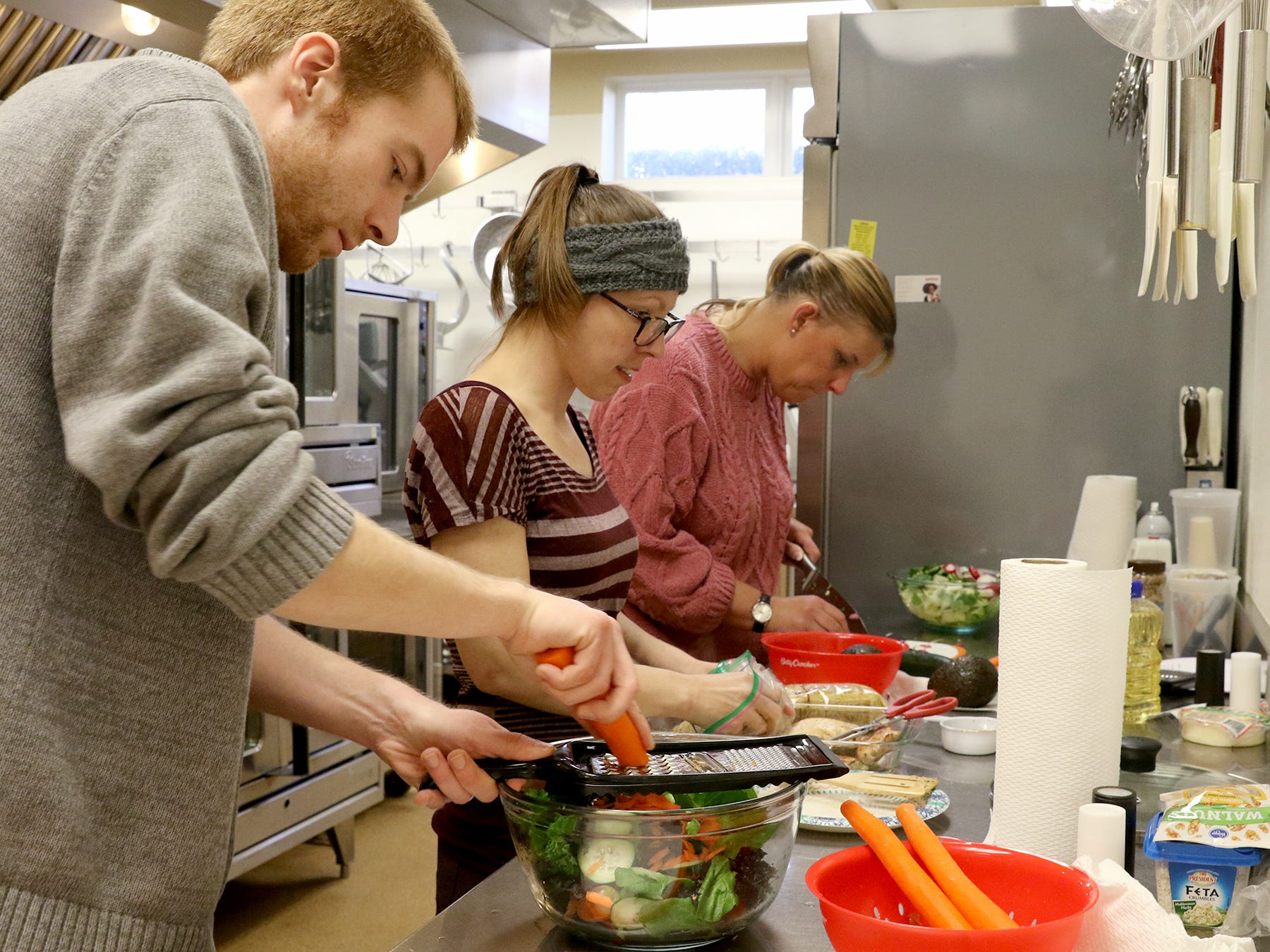 Craig Andrews (left) shreds carrots for his salad while sous chef Britney Doyle (center) shreds chicken and Brandy Mathews chops vegetables at Kitsap Community Resources kitchen in Bremerton on Thursday, February 21, 2019.