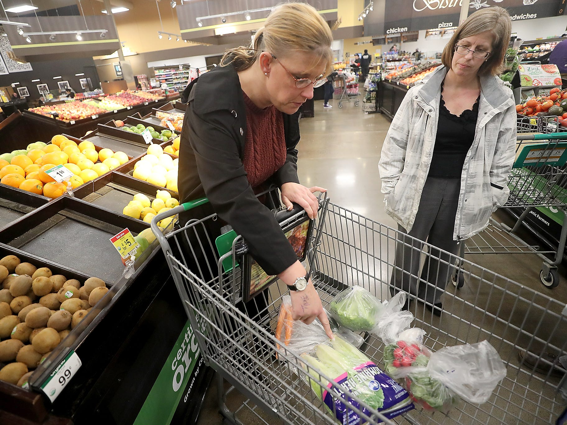 Brandy Mathews (left)  looks over the produce on her cart with Georgene Lenon at Fred Meyer in Bremerton on Wednesday, February 20, 2019.