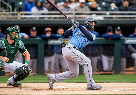 Seattle Mariners' Shed Long, right, doubles in the first inning against the Oakland Athletics during the first spring training baseball game of the season Thursday, Feb. 21, 2019, in Mesa, Ariz.