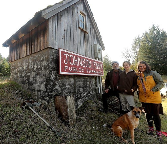 Mark Taylor, Quinn Lang and Tracy Lang with their dog Bandit at Bainbridge Island's Johnson Farm on Thursday. The family will be leasing a section of the farm and starting a hydroponic farm.
