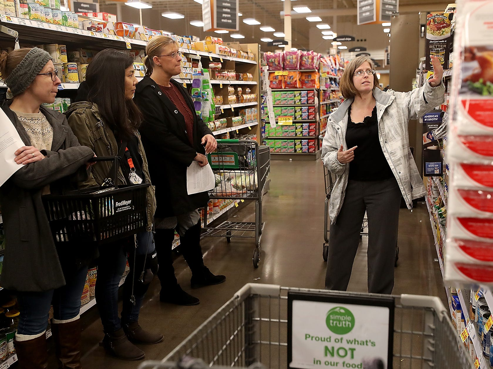 Kitsap Community Resources cooking class staff Sous Chef Britney Doyle (left), Shin Frost and class participant Brandy Mathews (center) listen as Georgene Lenon (right) talks about choosing the right soup stock and how to get the best value at Fred Meyer in Bremerton on Wednesday, February 20, 2019.