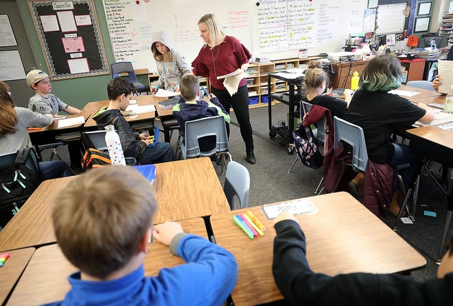 Fifth-grade teacher Kristy Dressler passes out assignments during class at Suquamish Elementary School on Thursday. Administrators in North Kitsap say the state's new funding formula following McCleary fixes will leave it short of revenue in the 2019-2020 school year. Other school districts in the state are in the same boat.