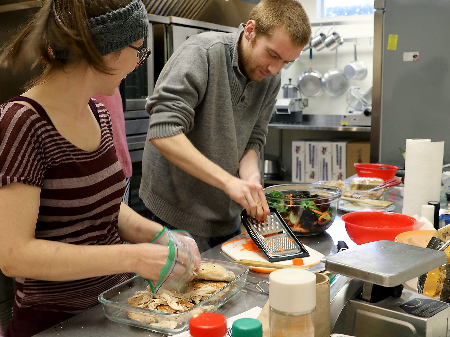 Craig Andrews shreds carrots under the watchful eye of sous chef Britney Doyle in Kitsap Community Resources kitchen in Bremerton on Thursday, February 21, 2019.