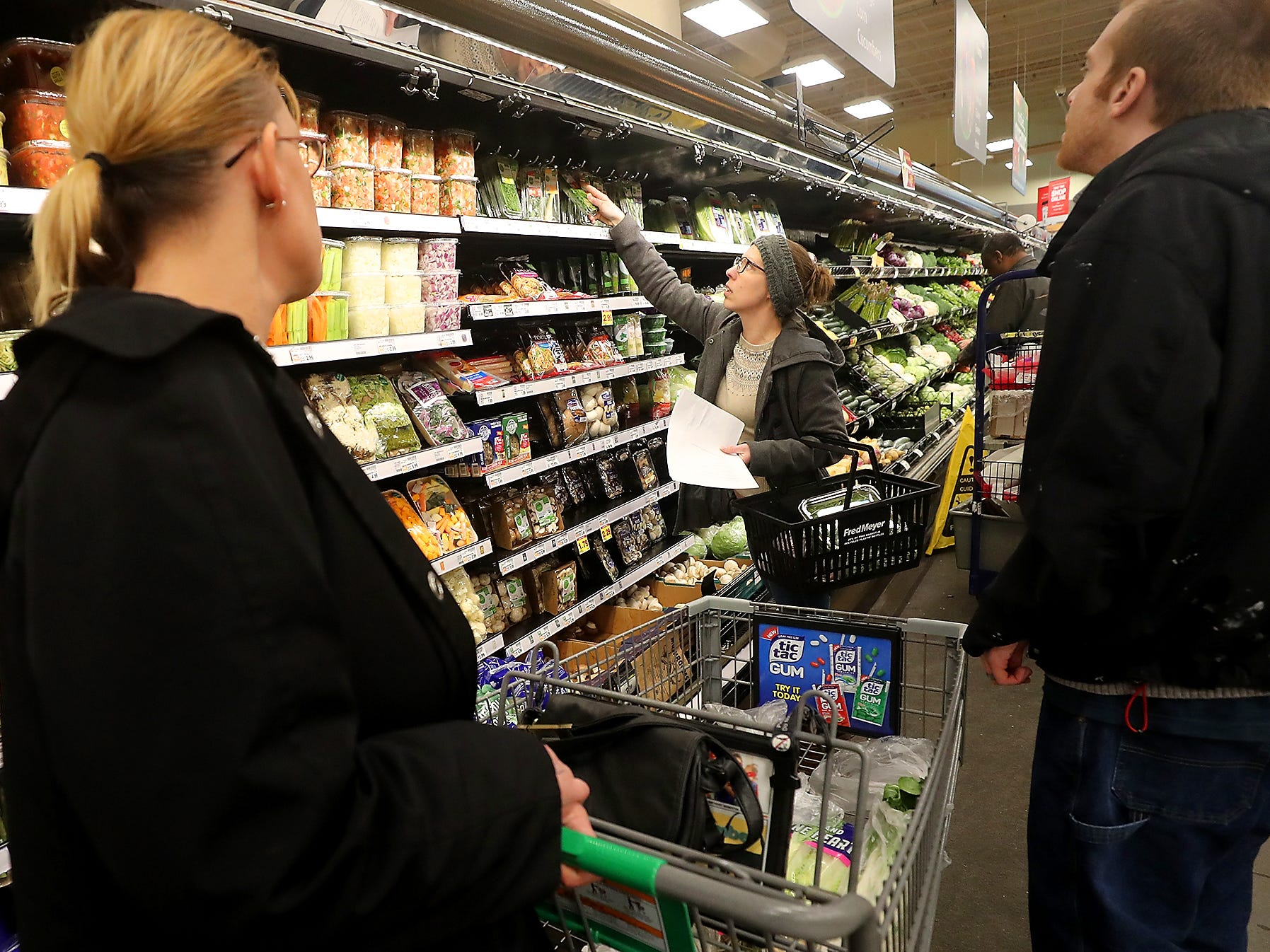 Sous chef Britney Doyle (center) talks about the different kind of fresh herbs available for their soup recipe as Brandy Mathews (left) and Craig Andrews (right) look on at Fred Meyer in Bremerton on Wednesday, February 20, 2019.