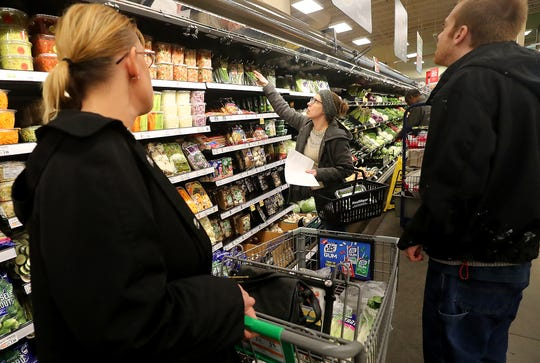 Sous chef Britney Doyle, center, talks about the different kind of fresh herbs available for a soup recipe as Brandy Mathews, left, and Craig Andrews, right, look on at Fred Meyer in Bremerton on Wednesday.
