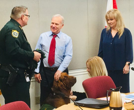 Brevard County Sheriff Wayne Ivey and bloodhound Junny meet with county commissioners during a break in Thursday's budget workshop. The sheriff is joined by Commissioner Curt Smith, County Commission Chair Kristine Isnardi and Commissioner Rita Pritchett.