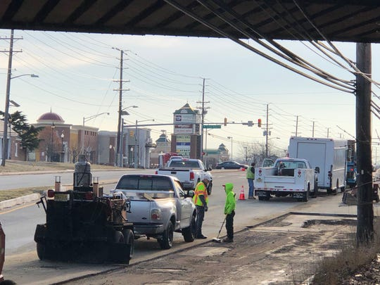 Workers patch a water-main break under an overpass of Route 70 in Cherry Hill.