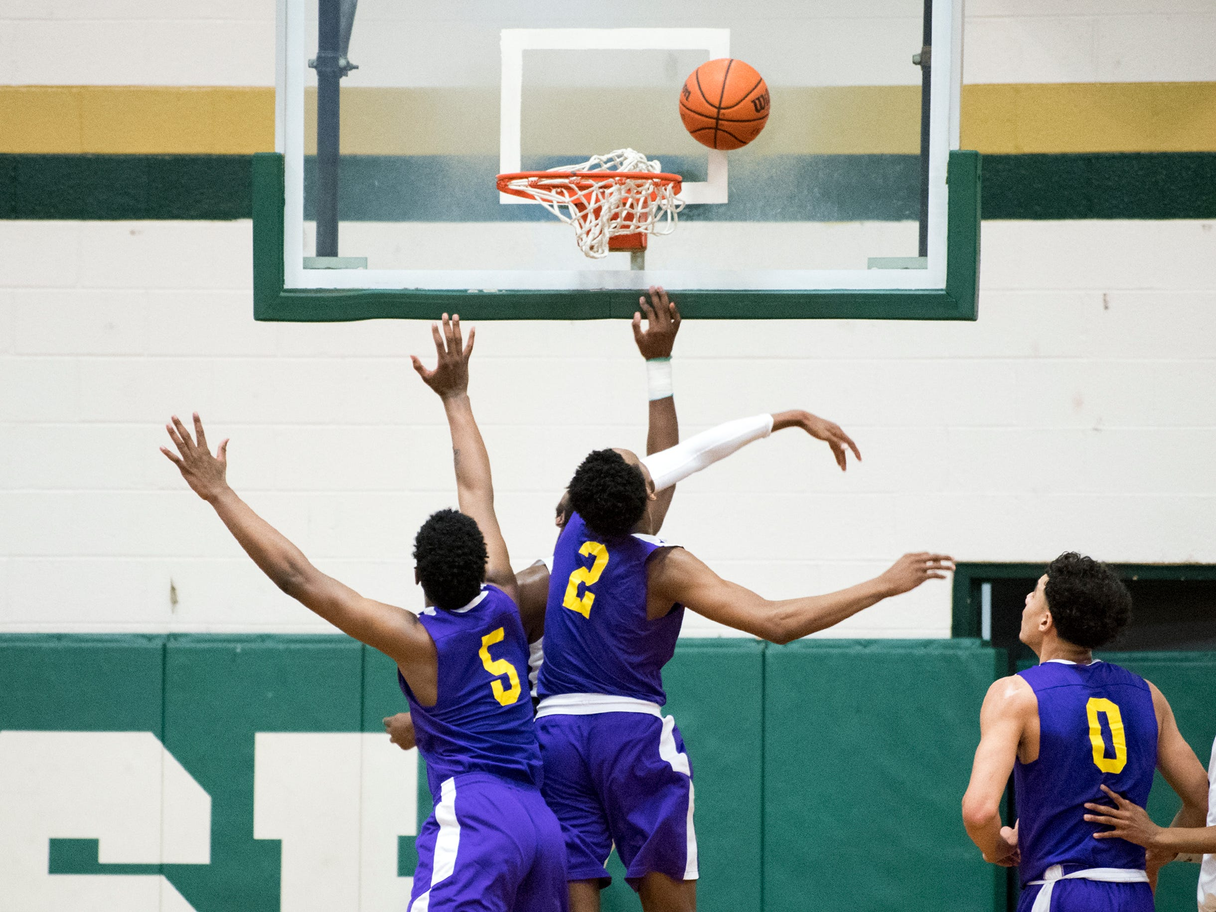 Camden's Taquon Woodley (5) and Jerome Brewer (2) attempt to block a shot from Camden Catholic Thursday, Feb. 21, 2019 at Camden Catholic High School in Cherry Hill, N.J. Camden Catholic won 57-54.