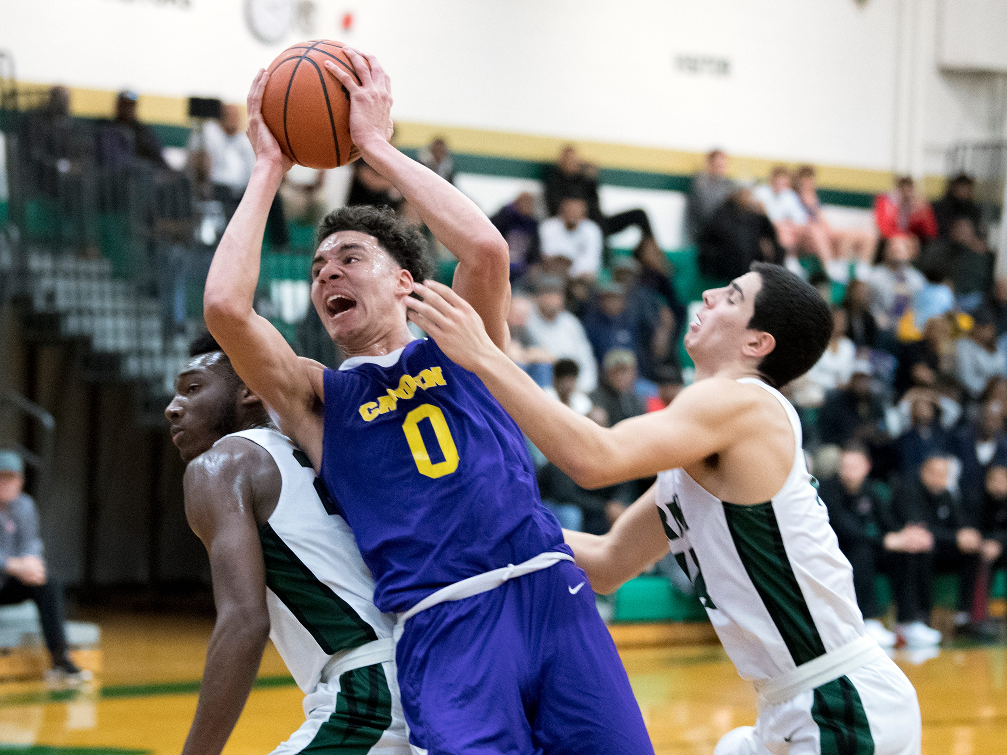 Camden's Lance Ware (0) pushes between Camden Catholic defenders Thursday, Feb. 21, 2019 at Camden Catholic High School in Cherry Hill, N.J. Camden Catholic won 57-54.