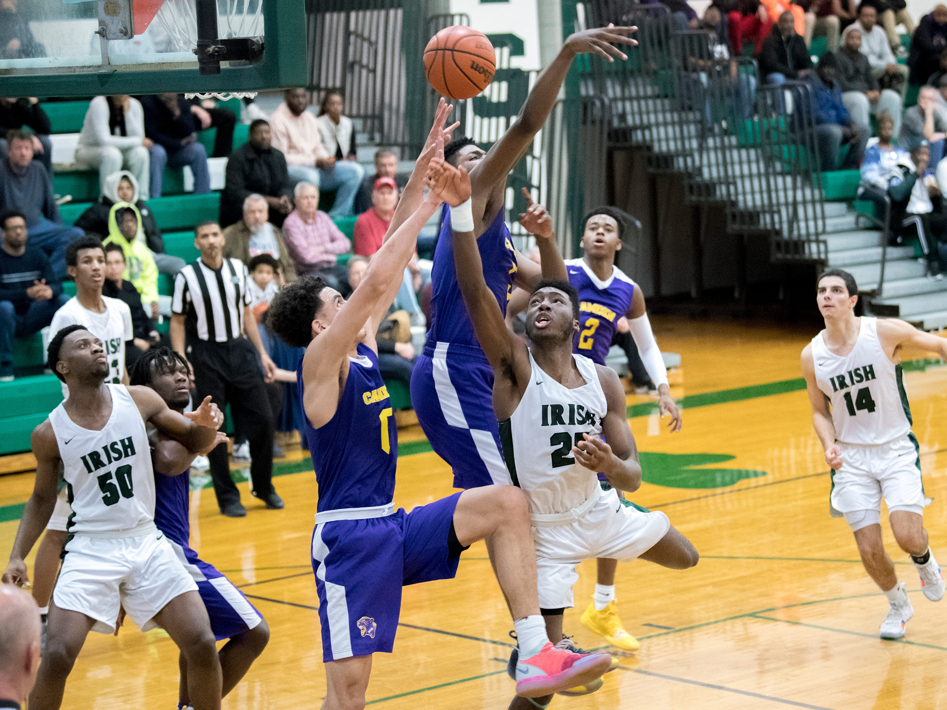 Camden's Lance Ware (0) and Camden Catholic's Babatunde Ajike (25) battle for possession Thursday, Feb. 21, 2019 at Camden Catholic High School in Cherry Hill, N.J. Camden Catholic won 57-54.