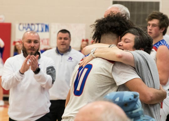 After scoring his 1000-point, Cam Evans hugs his mother Beth as his coaches clap and congratulate the Zane Trace junior during a momentous game against Adena.