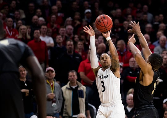 Cincinnati Bearcats guard Justin Jenifer (3) hits a 3-pointer over UCF Knights guard B.J. Taylor (1) putting Cincinnati Bearcats up by 5 late in the second half of the NCAA men's basketball game between Cincinnati Bearcats and UCF Knights on Thursday, Feb. 21, 2019, at Fifth Third Arena in Cincinnati.