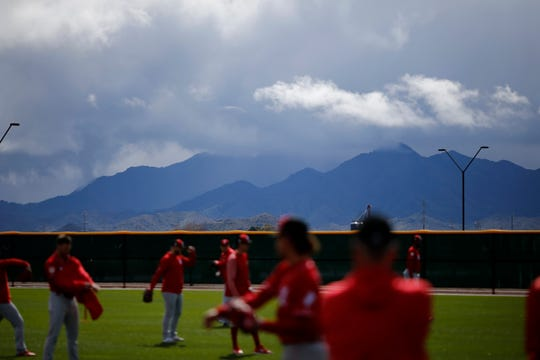 Cincinnati Reds pitchers warmup at the Cincinnati Reds spring training facility in Goodyear, Ariz., on Friday, Feb. 22, 2019.