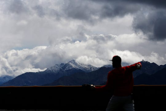 Cincinnati Reds outfielder Matt Kemp (27) long tosses silhouetted in front of a snow-capped Estrella Mountain top at the Cincinnati Reds spring training facility in Goodyear, Ariz., on Friday, Feb. 22, 2019.