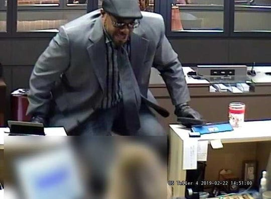 A man wearing a gray suit with black dress shoes, glasses and black gloves robbed a bank Friday in Sycamore Township