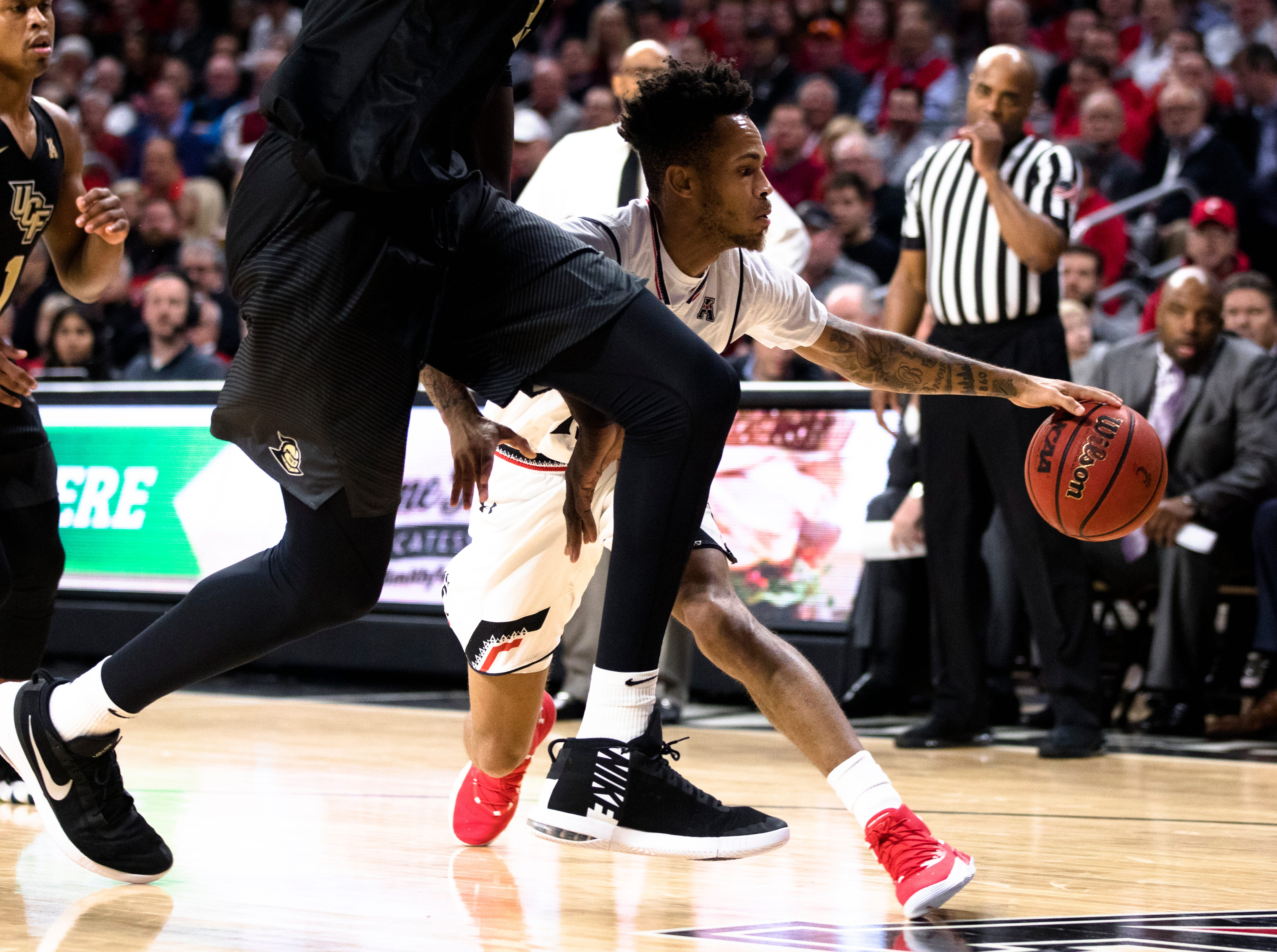 Cincinnati Bearcats guard Cane Broome (15) drives on UCF Knights center Tacko Fall (24) in the first half of the NCAA men's basketball game between Cincinnati Bearcats and UCF Knights on Thursday, Feb. 21, 2019, at Fifth Third Arena in Cincinnati.