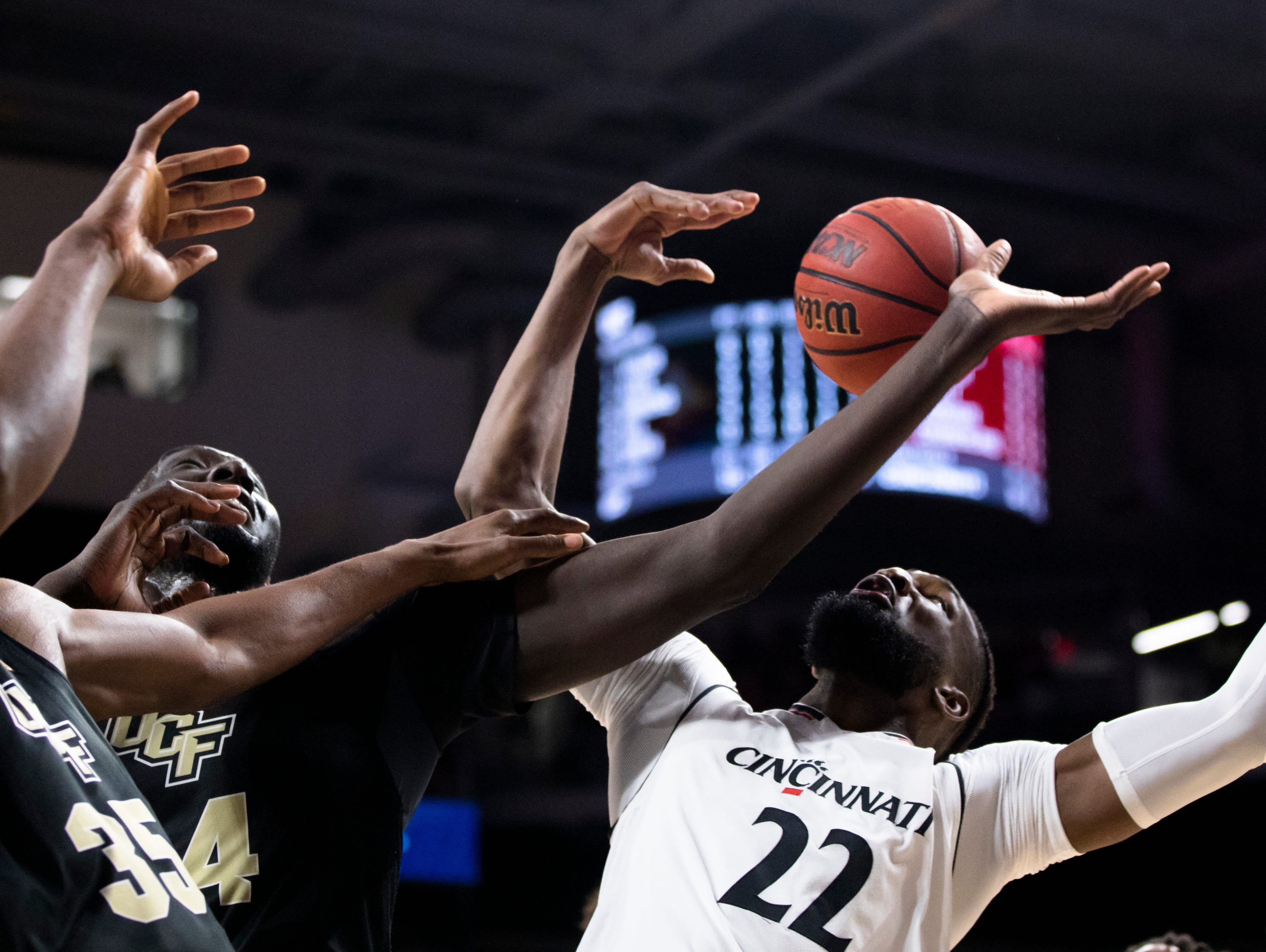 Cincinnati Bearcats forward Eliel Nsoseme (22) fights for a rebound with UCF Knights center Tacko Fall (24) in the first half of the NCAA men's basketball game between Cincinnati Bearcats and UCF Knights on Thursday, Feb. 21, 2019, at Fifth Third Arena in Cincinnati.