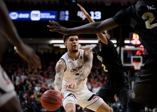 Cincinnati Bearcats guard Jarron Cumberland (34) passes as UCF Knights guard Terrell Allen (2) guards him in the first half of the NCAA men's basketball game between Cincinnati Bearcats and UCF Knights on Thursday, Feb. 21, 2019, at Fifth Third Arena in Cincinnati.