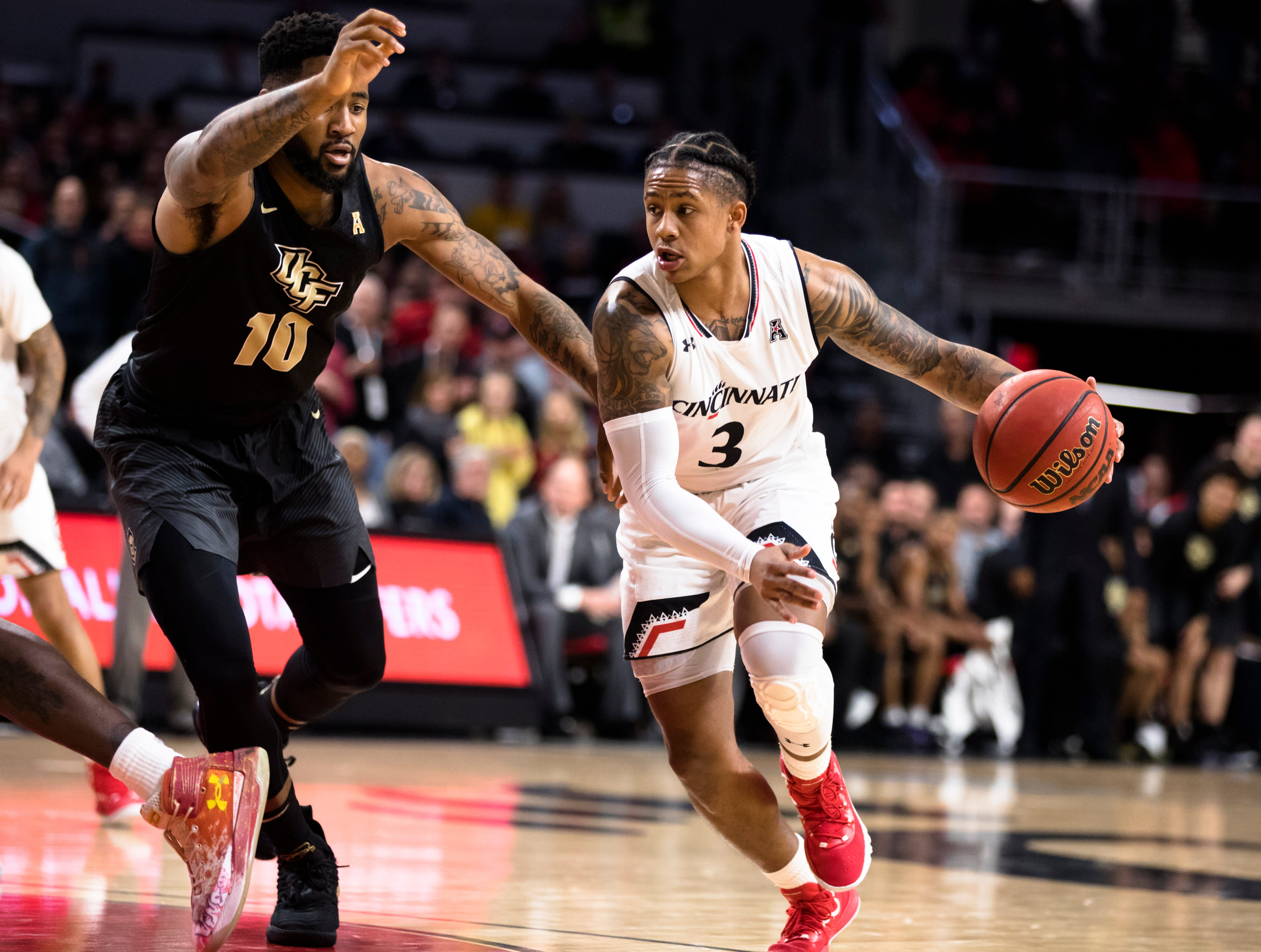 Cincinnati Bearcats guard Justin Jenifer (3) drives on UCF Knights guard Dayon Griffin (10) in the second half of the NCAA men's basketball game between Cincinnati Bearcats and UCF Knights on Thursday, Feb. 21, 2019, at Fifth Third Arena in Cincinnati.