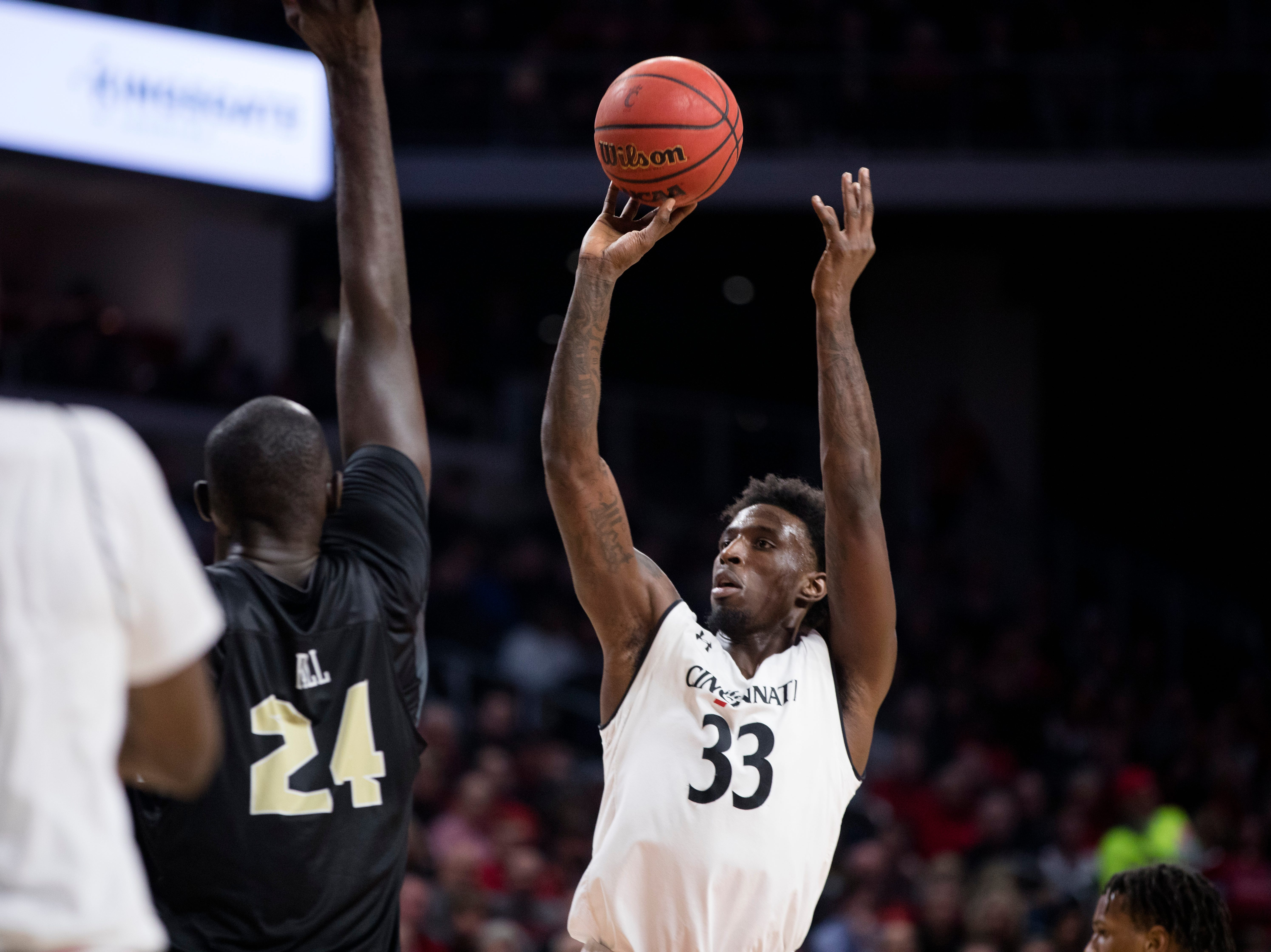 Cincinnati Bearcats center Nysier Brooks (33) shoots over UCF Knights center Tacko Fall (24) in the second half of the NCAA men's basketball game between Cincinnati Bearcats and UCF Knights on Thursday, Feb. 21, 2019, at Fifth Third Arena in Cincinnati.