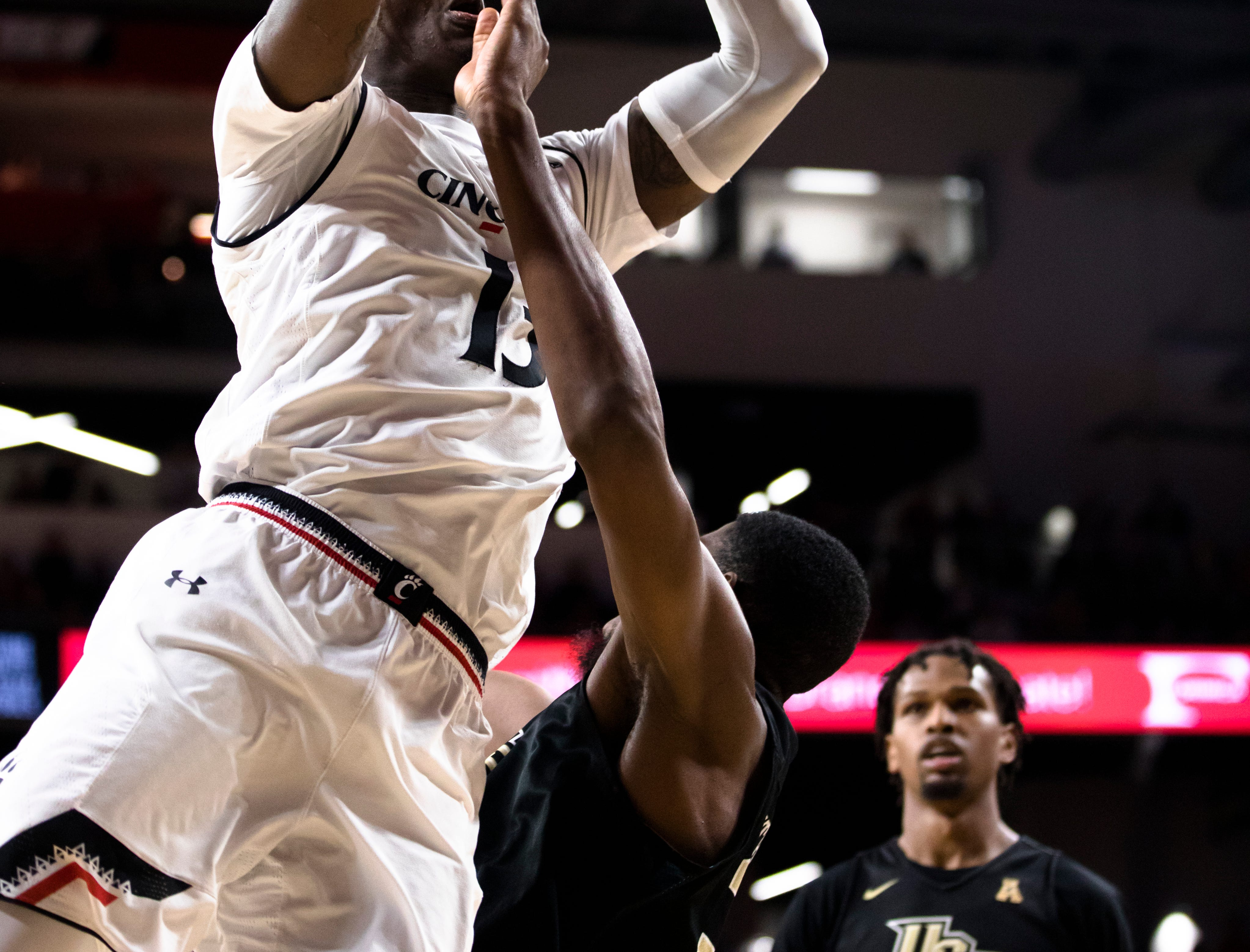 Cincinnati Bearcats forward Trevon Scott (13) shoots as UCF Knights forward Collin Smith (35) draws a charge call in the first half of the NCAA men's basketball game between Cincinnati Bearcats and UCF Knights on Thursday, Feb. 21, 2019, at Fifth Third Arena in Cincinnati.