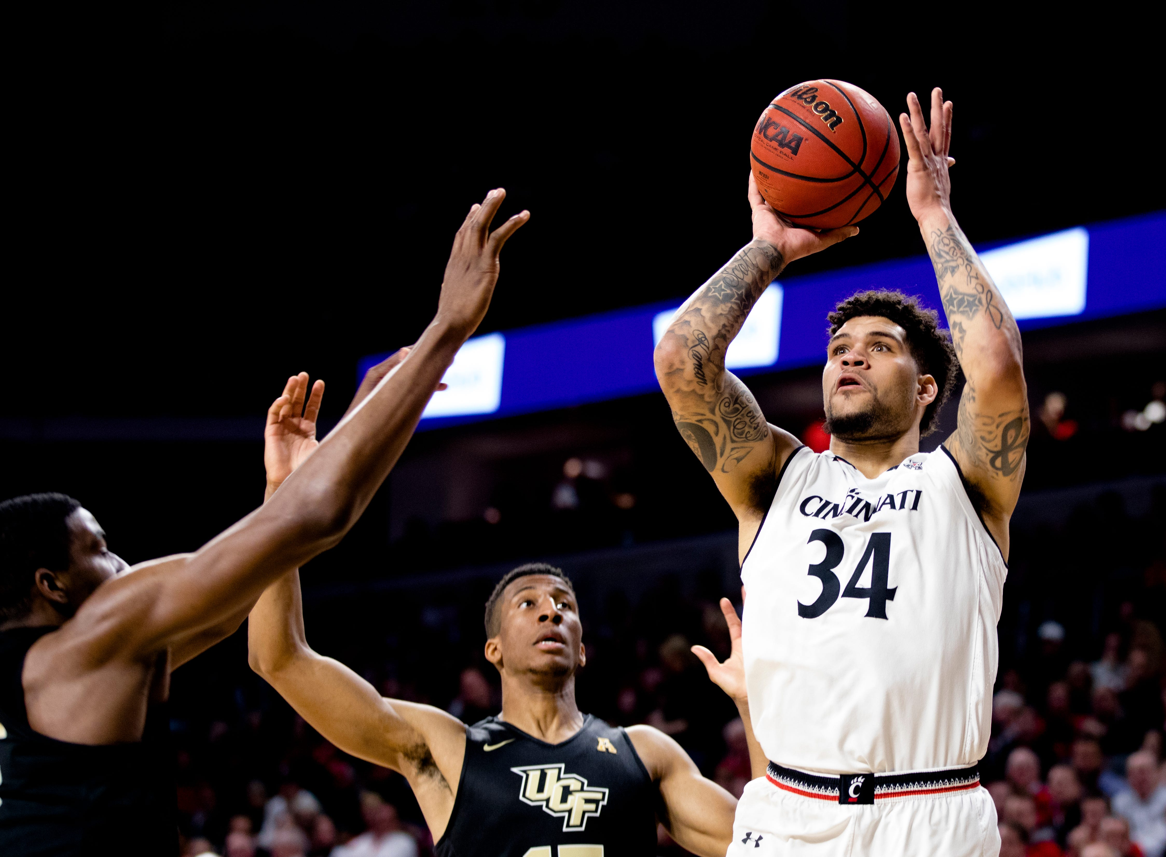 Cincinnati Bearcats guard Jarron Cumberland (34) shoots as UCF Knights forward Collin Smith (35) guards him in the first half of the NCAA men's basketball game between Cincinnati Bearcats and UCF Knights on Thursday, Feb. 21, 2019, at Fifth Third Arena in Cincinnati.