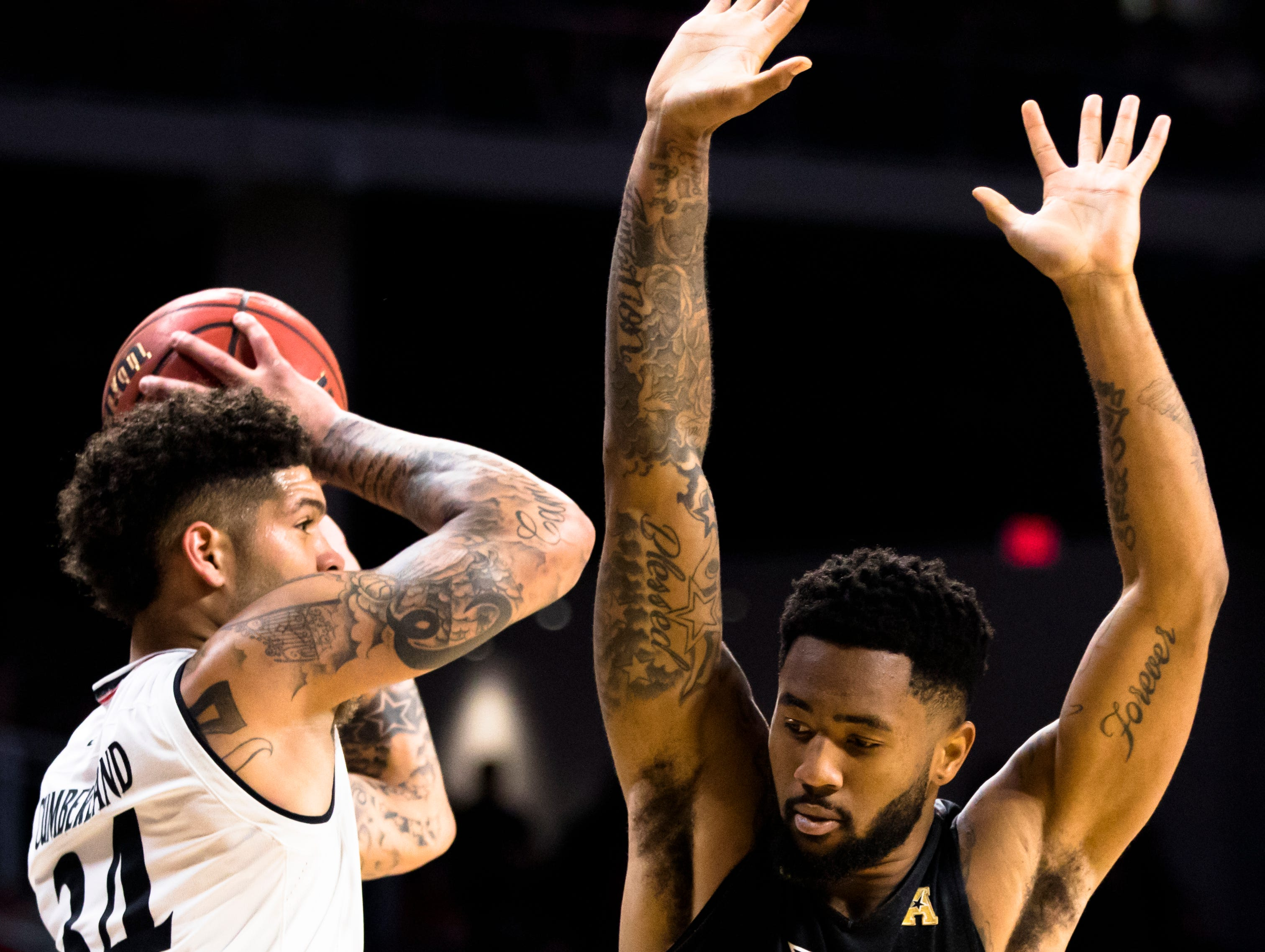 Cincinnati Bearcats guard Jarron Cumberland (34) passes as UCF Knights guard Dayon Griffin (10) guards him in the first half of the NCAA men's basketball game between Cincinnati Bearcats and UCF Knights on Thursday, Feb. 21, 2019, at Fifth Third Arena in Cincinnati.