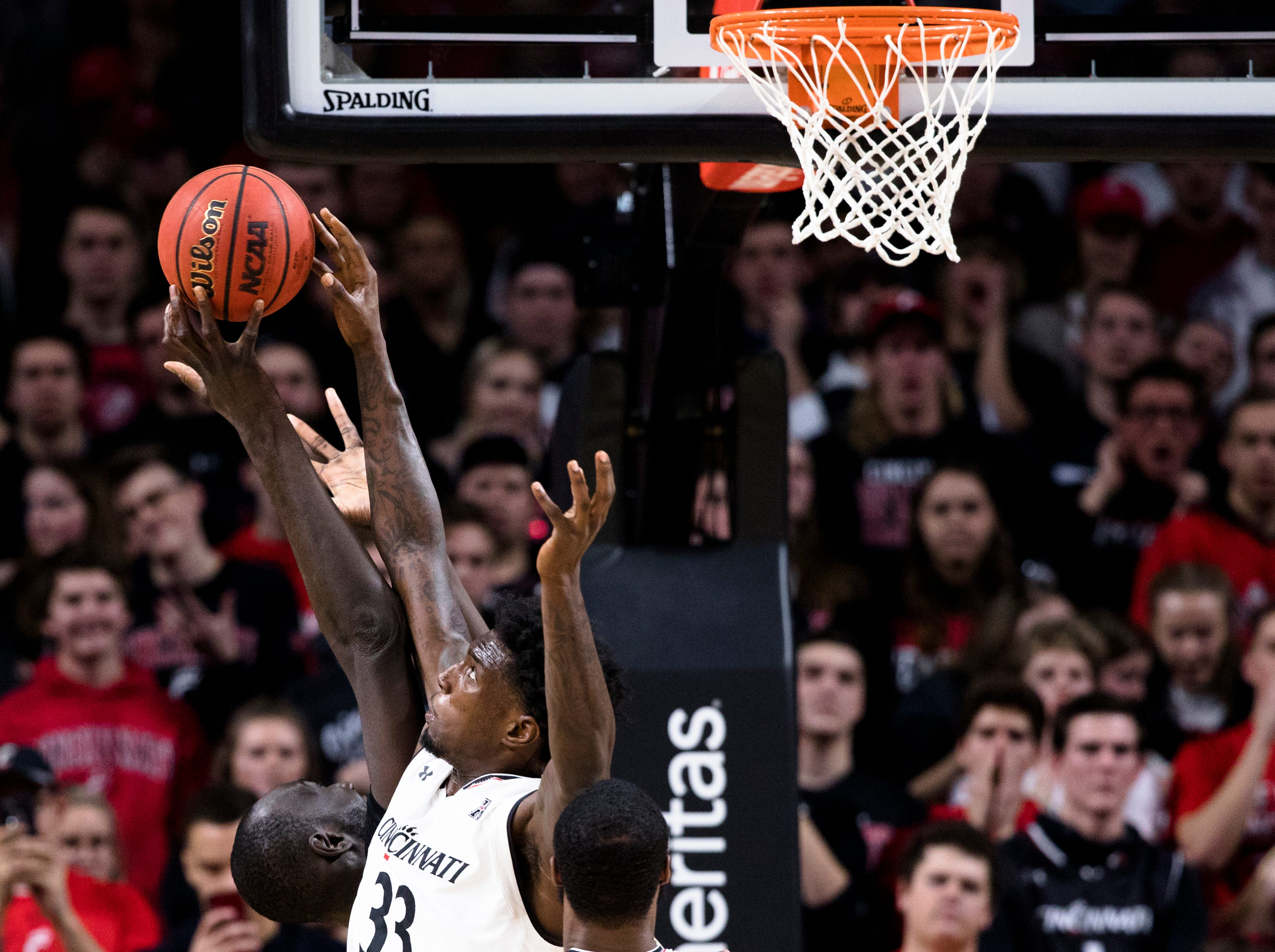 Cincinnati Bearcats center Nysier Brooks (33) fights for a rebound with UCF Knights center Tacko Fall (24) in the first half of the NCAA men's basketball game between Cincinnati Bearcats and UCF Knights on Thursday, Feb. 21, 2019, at Fifth Third Arena in Cincinnati.