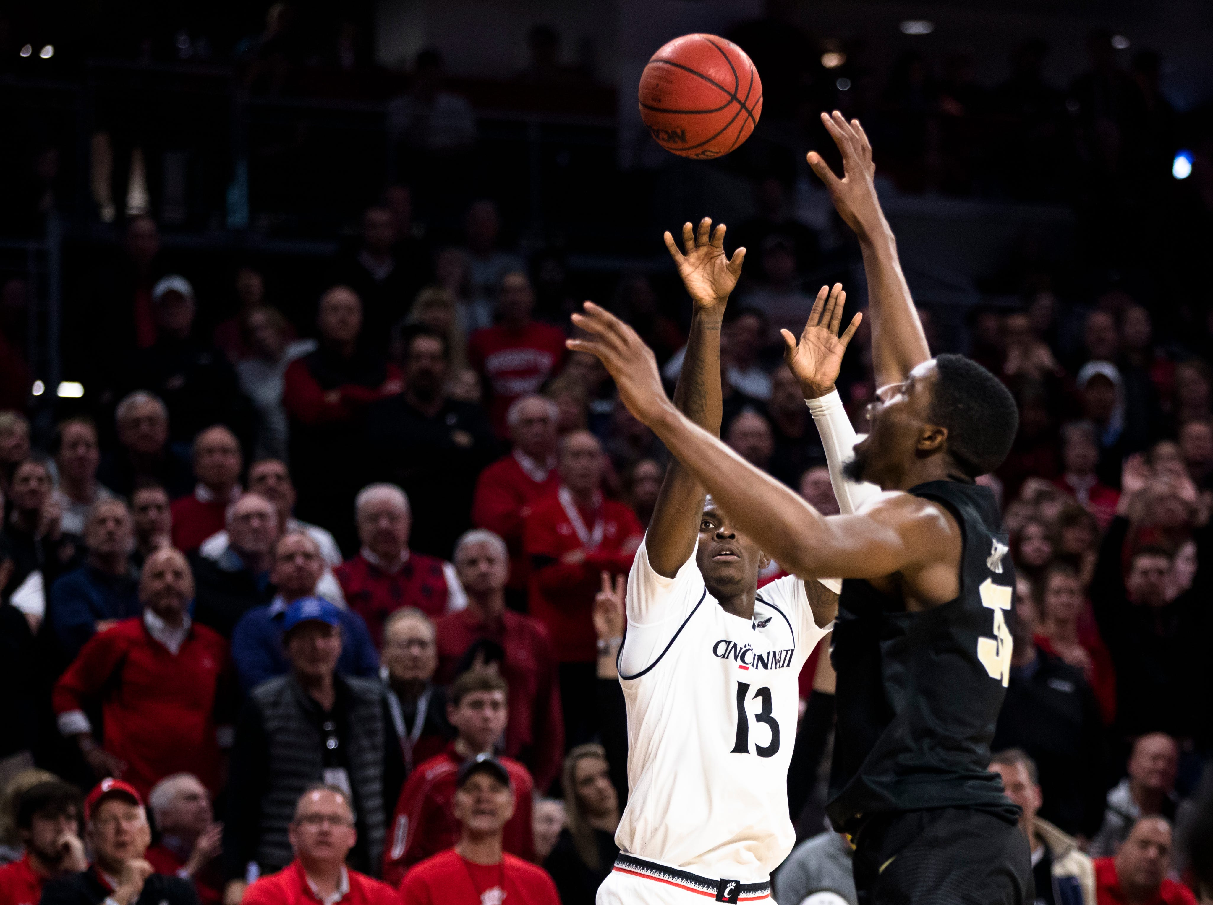 Cincinnati Bearcats forward Trevon Scott (13) hits a 3-pointer over UCF Knights forward Collin Smith (35) in the second half of the NCAA men's basketball game between Cincinnati Bearcats and UCF Knights on Thursday, Feb. 21, 2019, at Fifth Third Arena in Cincinnati.