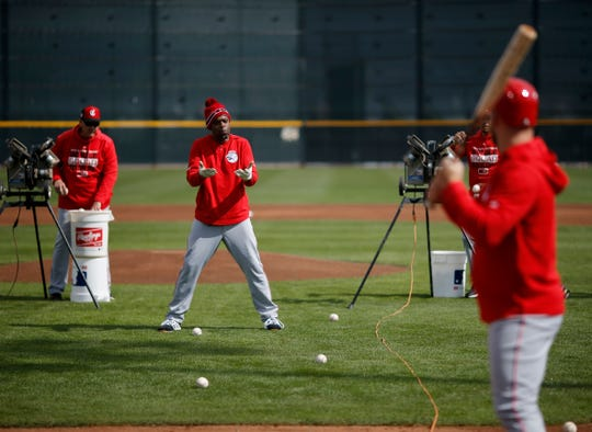 Cincinnati Reds first base coach Delino DeShields works with pitchers in bunting drills at the Cincinnati Reds spring training facility in Goodyear, Ariz., on Friday, Feb. 22, 2019.