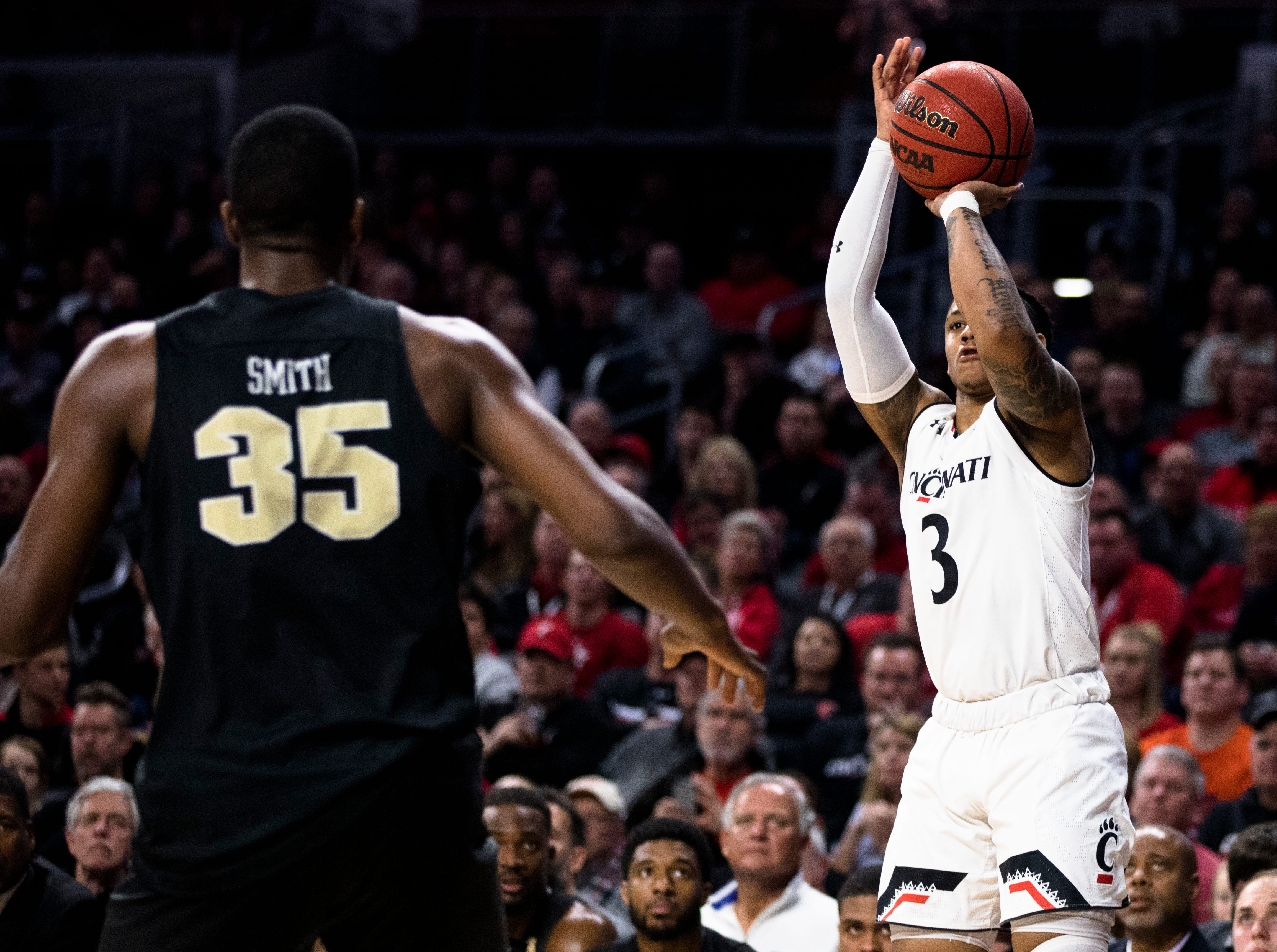 Cincinnati Bearcats guard Justin Jenifer (3) shoots a 3-pointer over UCF Knights forward Collin Smith (35) in the first half of the NCAA men's basketball game between Cincinnati Bearcats and UCF Knights on Thursday, Feb. 21, 2019, at Fifth Third Arena in Cincinnati.