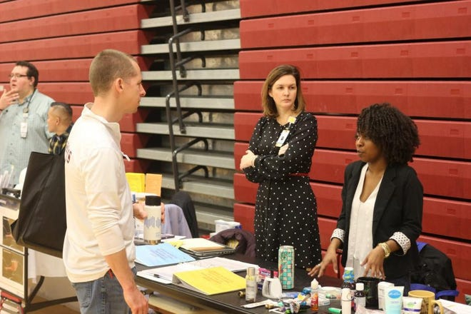 Ross High School science teacher Brian Streng receives tips on how to properly hydrate at the TriHealth Wellness Fair.
