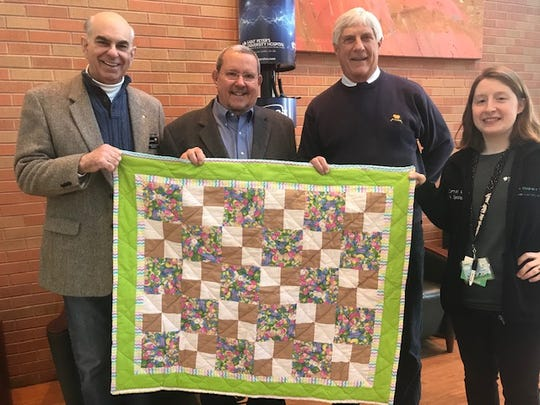 Delivering quilts on behalf of Quilts for Kids are Andrew S. Casella, Thomas Monroe and Edward Koch representing Council #15540. Receiving the quilts for St. Peter's is Alexa Curtiss, Certified Child Life Specialist.