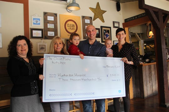 (Left to right)Amy Tiederman, PhD, director of Development, Hunterdon Healthcare Foundation;Janet McCulloch, LCSW, Hunterdon Hospice Social Worker, accept a check to Hunterdon Hospice from the owners of The Clean Plate Kitchen in Clinton, Anthony and Nicole Piazza with their daughters, Zinnia, age 2 and Talulla, 8 months.