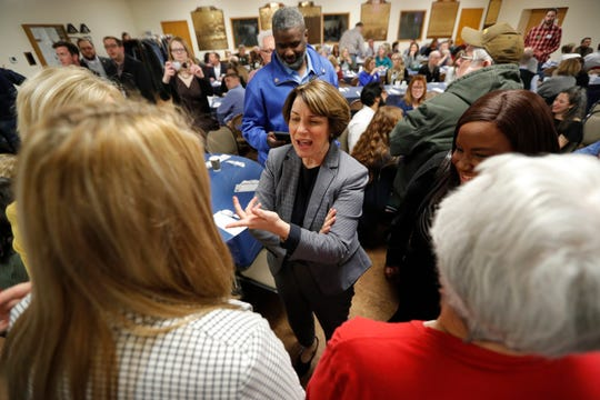 Democratic presidential candidate Amy Klobuchar, center, greets local residents at the Ankeny Area Democrats' winter banquet on Thursday, Feb. 21, 2019, in Des Moines, Iowa.