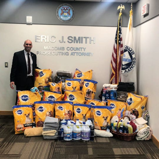 Macomb County Prosecutor Eric Smith stands with donations from his staff and staff at the Friend of the Court for the 52 dogs turned over to the county's animal control Feb. 13, 2019, after what officials believed was a hoarding situation at a home in Sterling Heights.