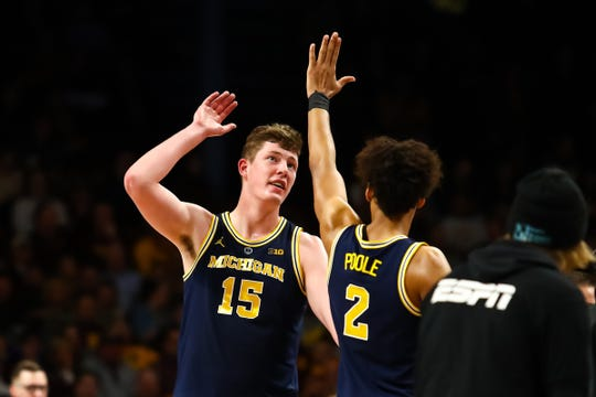 Michigan center Jon Teske (15) and guard Jordan Poole celebrate during a timeout in the second half against Minnesota, Thursday, Feb. 21, 2019, in Minneapolis.